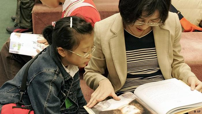 A South Korean woman reads a book with her daughter in Seoul