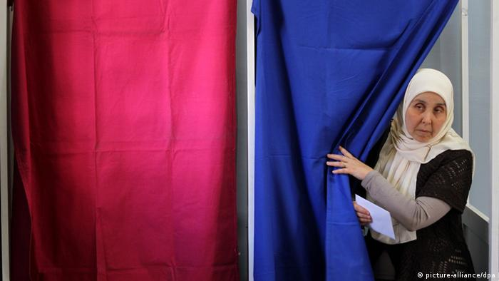 An Algerian woman comes out of the voting booth