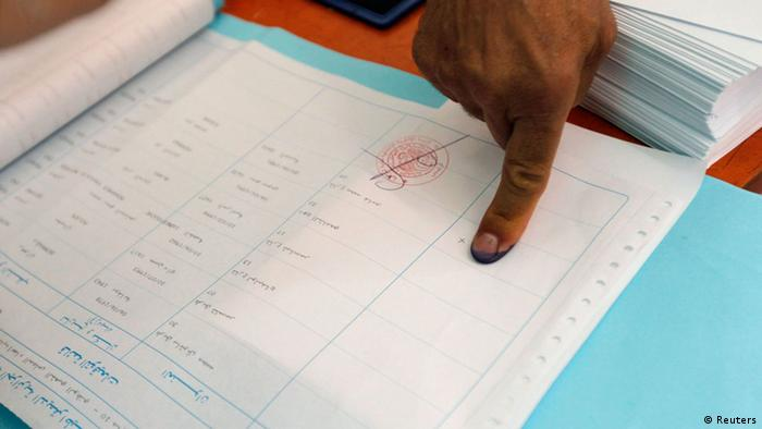 An Algerian man registers his thumbprint as he prepares to cast his ballot during parliamentary elections.
