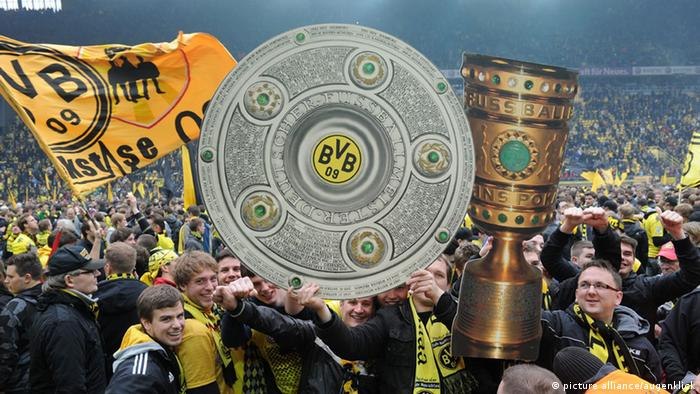 Dortmund fans celebrating, with images of the German Bundesliga and German Cup trophies