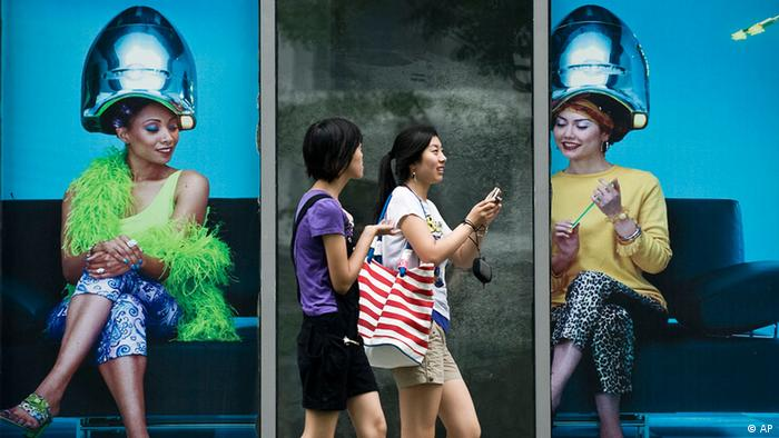 Chinese women walk past a commercial shop lot displaying a poster of women doing hairstyle in Beijing, China, Monday, July 13, 2009. Economists have pointed to increased activity in residential and commercial real estate as signs China is emerging from its slump as Beijing's 4 trillion yuan (US$586 billion) stimulus plan pumps money into the economy. (Photo: Andy Wong/AP)