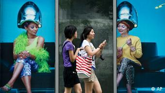 Chinese women walk past a commercial shop lot displaying a poster of women getting their hair done in Beijing