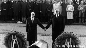 François Mitterrand und Helmut Kohl Hand in Hand vor Kränzen in Verdun (Foto: picture alliance/dpa)