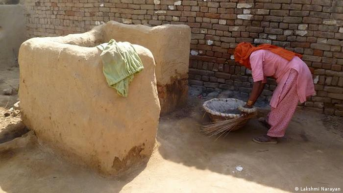 A woman prepares to clean a dry latrine in a poor farmer's house in Mudali