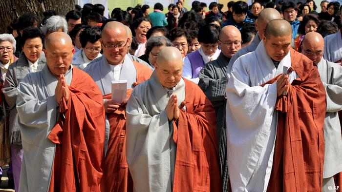 South Korean Buddhist monks and believers pay silent tribute to victims of Friday's earthquake and tsunami in Japan before launching a fund raising campaign at the Jogye Temple in Seoul, South Korea, Tuesday, March 15, 2011. (ddp images/AP Photo/ Lee Jin-man).