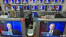 Russian President Vladimir Putin seen on television screens in a shop as he answers questions during an online conference in Moscow, Thursday, July 6, 2006. President Vladimir Putin on Thursday was to answer questions from Russian and foreign Web surfers during a live Internet conference, part of a charm offensive ahead of next week's Group of Eight Industrialized nations summit in Russia. (AP Photo/Misha Japaridze)