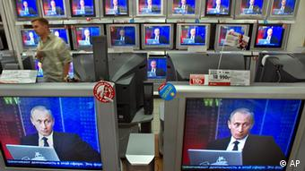 Russian President Vladimir Putin seen on television screens in a shop (AP Photo/Misha Japaridze)
