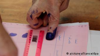 An Algerian man signs with his fingerprint as he prepares to vote