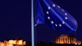 The European Union flag flutters in the wind with the ancient Parthenon temple, right, and the Propylaea, left, at the Acropolis Hill, in Athens on Tuesday, Oct. 25, 2011