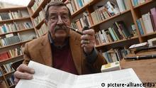 ARCHIV - Der Literaturnobelpreisträger Günter Grass sitzt am 05.04.2012 in seinem Atelier in Behlendorf und hält sein umstrittenes Israel-Gedicht hoch. Die Vereinigung von Schriftstellern wird vom 10. bis 13. Mai 2012 hier seine Jahrestagung abhalten. Das deutsche PEN-Zentrum wird bei seiner Mitgliederversammlung am Samstag (12.05.2012) über eine Aberkennung der Ehrenpräsidentschaft von Günter Grass beraten. Foto: Marcus Brandt dpa/lth (zu lth vom 11.05.2012) +++(c) dpa - Bildfunk+++