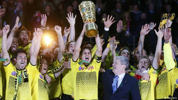 Borussia Dortmund players celebrate with the trophy after defeating Bayern Munich to win the German DFB Cup (DFB Pokal) final soccer match at the Olympic stadium in Berlin, May 12, 2012. Dortmund won the match 5-2. At centre right is German President Joachim Gauck. REUTERS/Photographer Name (GERMANY) REUTERS/Kai Pfaffenbach (GERMANY - Tags: SPORT SOCCER) DFB RULES PROHIBIT USE IN MMS SERVICES VIA HANDHELD DEVICES UNTIL TWO HOURS AFTER A MATCH AND ANY USAGE ON INTERNET OR ONLINE MEDIA SIMULATING VIDEO FOOTAGE DURING THE MATCH