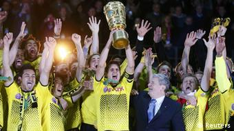 Borussia Dortmund players celebrate with the trophy after defeating Bayern Munich to win the German DFB Cup (DFB Pokal) final soccer match at the Olympic stadium in Berlin, May 12, 2012.