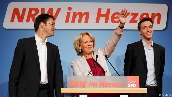 Hannelore Kraft, federal state premier of North-Rhine Westphalia (NRW) and top candidate of the Social Democratic Party (SPD) stands next to her husband Udo and son Jan as she addresses supporters after first exit polls for the NRW federal state election in Duesseldorf May 13, 2012. Chancellor Angela Merkel's conservatives suffered a crushing defeat on Sunday in an election in Germany's most populous state, a result which could embolden the left opposition to step up its criticism of her European austerity policies. REUTERS/Wolfgang Rattay (GERMANY - Tags: POLITICS ELECTIONS)