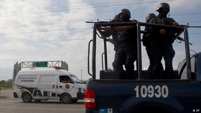 Federal police on a vehicle guard one of the three forensic trucks where several bodies were placed after dozens of bodies, some of them mutilated, were found on a highway connecting the northern Mexican metropolis of Monterrey to the U.S. border found in the Km 47 of the Reynosa-Cadereyta road in the town of San Juan near the city of Monterrey, Mexico
