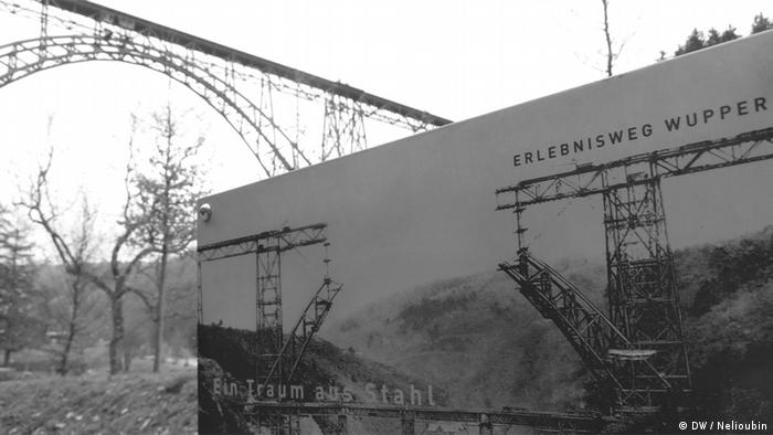 Информационное табло в парке около моста с фотографией 1897 года. Фото: DW / Максим Нелюбин