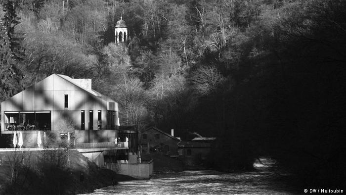 Информационный центр с кафе. За ним у реки - старая кузнечная мастерская. На склоне - беседка около прогулочной дорожки. Фото: DW / Максим Нелюбин