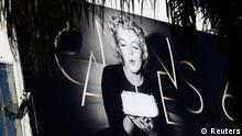 A worker sets up a giant canvas of the official poster of the 65th Cannes Film Festival featuring U.S. actress Marilyn Monroe on the facade of the Festival Palace in Cannes May 14, 2012. The Cannes film festival will run from May 16 to 27. REUTERS/Eric Gaillard (FRANCE - Tags: ENTERTAINMENT)