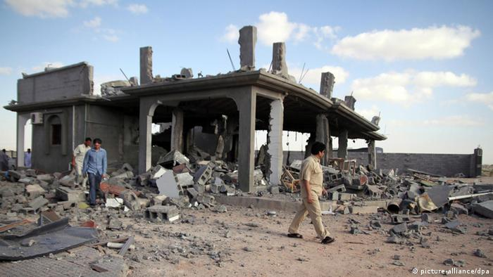 Libyan men walk past destroyed buildings on August 10, 2011, in Majer