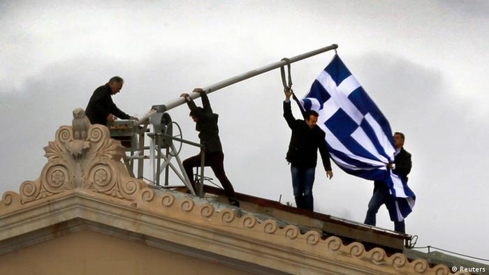 Parliament employees raise a mast after they replaced a torn-off Greek flag with a new one atop the parliament in Athens