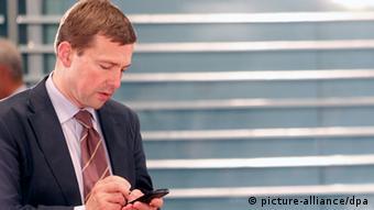 German government spokesman Steffen Seibert types on his smartphone at a press engagement.