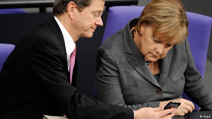 German Chancellor Angela Merkel and Foreign Minister Guido Westerwelle look at a smartphone in parliament.