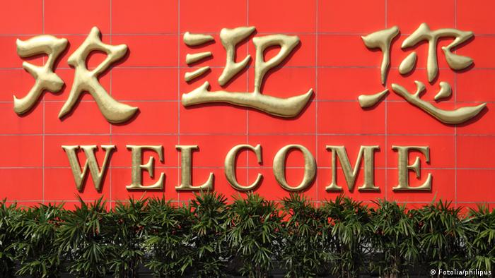 Chinese letters saying Welcome across red wall