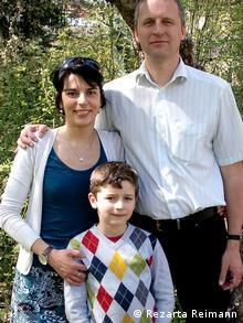 """Rezarta Reimann (Meço) ist in Tirana geboren und kam 1998 wegen einer Promotionsarbeit nach Jena, wo sie ihren heuitigen Mann kennenlernte. Sie lebt mit ihm und ihrem Sohn in Schwabach nahe Nürnberg, wo sie Biologie an der Uni unterrichtet. Die dreiköpfige Familie hat zwischendurch auch in Albanien gelebt. In der Serie """"Albaner in Deutschland"""" erzählt Rezarta Reimann, was ihr in Deutschland manchmal fehlt. Das Bild zeigt sie mit ihrem Mann und ihrem Sohn. Das Foto wurde die Familie sie in einem Seminarraum des Pädagogischen Fakultäts der Universität Nürnberg. Das Foto wurde im März 2012 von Anila Shuka aufgenommen."""