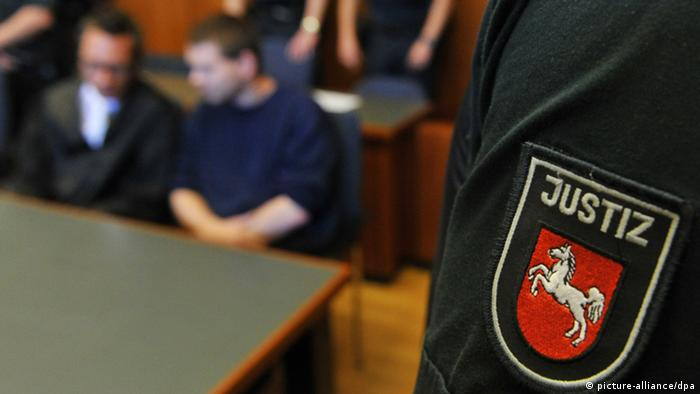 A courtroom scene, with two people sitting behind a table and a court official in front Photo: Jochen Lübke dpa/lni