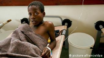 A young African boy, emaciated from illness, stares at the camera while sitting upright in his hospital bed. (Photo: AARON UFUMELI/EPA/dpa)