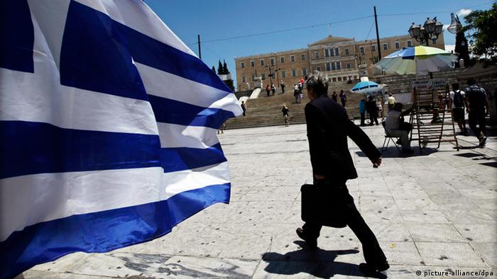 epa03219896 A Greek flag waves at Syntagma square in front of the Greek Parliament as pedestrians walk by, in Athens, Greece, 15 May 2012. Greece's president was in meetings on 15 May with the leaders of five political parties that could see them surrender the reins of power to a new government made up of technocrats, an effort to resolve the political deadlock which risks forcing the country into new elections and out of the eurozone. Party leaders have been squabbling for the past week over whether the country should continue down the path of harsh austerity measures prescribed by the EU and the IMF - or pull out of a bailout deal. Coalition talks have failed so far after the Coalition of the Radical Left or SYRIZA, which came second in the vote, insisted that the terms of an international bailout from the European Union and the International Monetary Fund (IMF) be scrapped or largely renegotiated. EPA/ALKIS KONSTANTINIDIS +++(c) dpa - Bildfunk+++
