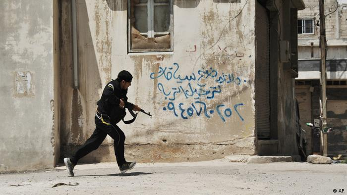 A Syrian rebel runs for cover at the Sunni district of Jabb al-Jandali in Homs, Syria, Monday, May 14, 2012.