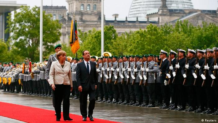 German Chancellor Angela Merkel and French President Francois Hollande review the guard of honour at the Chancellery in Berlin, May 15, 2012. Hollande called for a European pact for growth to balance out German-driven austerity measures in his inaugural address on Tuesday, hours before taking his challenge to Chancellor Angela Merkel in Berlin. Sworn in with all the pomp of the French Republic, Hollande won support from Germany's opposition Social Democrats (SPD), who vowed to use their parliamentary blocking power to delay ratifying a European budget discipline treaty until Merkel accepts accompanying measures to boost growth and jobs. REUTERS/Fabrizio Bensch (GERMANY - Tags: POLITICS)