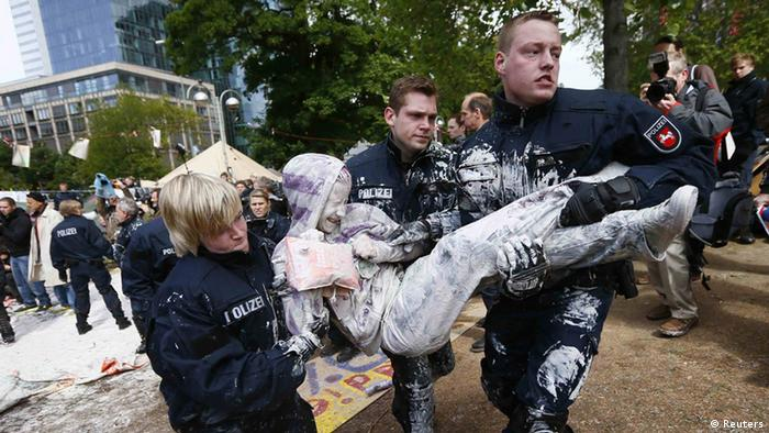 German riot police carry a demonstrator fully covered in paint as police clears the camp of occupy protestors in front of the European Central Bank (ECB) in Frankfurt, May 16, 2012. REUTERS/Kai Pfaffenbach (GERMANY - Tags: CIVIL UNREST POLITICS)