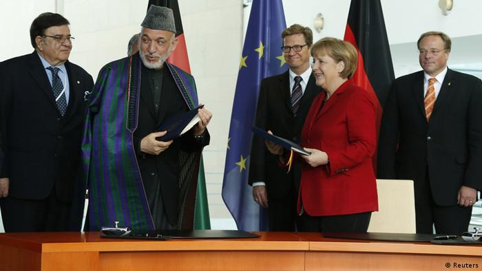 German Chancellor Angela Merkel and Afghan President Hamid Karzai sign documents during a ceremony for a bilateral cooperation agreement at the chancellery in Berlin, May 16, 2012. REUTERS/Fabrizio Bensch (GERMANY - Tags: POLITICS)