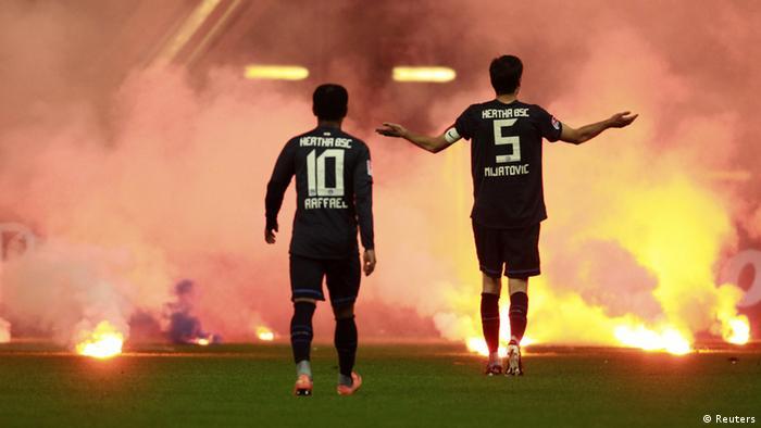 Два футболиста на фоне огня и дыма на стадионе