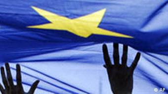 Hands hold up an EU flag