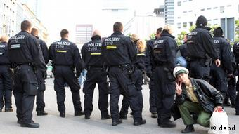 A woman dressed up as a police officer poses behind a police chain guarding a demonstration in Frankfurt, Germany, Wednesday, May 16, 2012. The demonstration was the beginning of the so called Blockupy days, where clashes between anti-capitalism demonstrators and police are expected. (Foto:Michael Probst/AP/dapd).