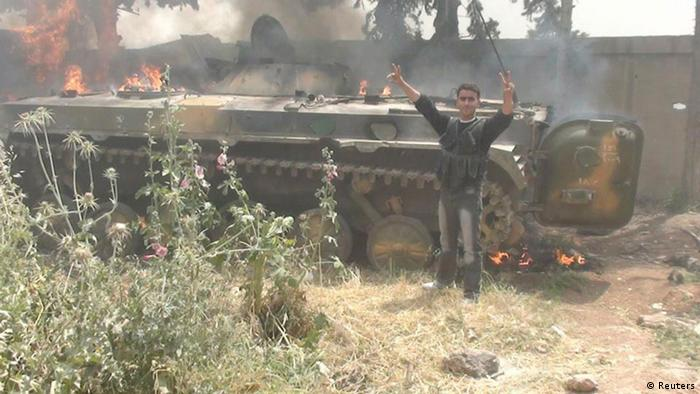Source News Feed: EMEA Picture Service ,Germany Picture Service A member of the Free Syrian Army celebrates in front of a burning tank after defeating government troops in Rasten, near Homs, May 14, 2012. Picture taken May 14, 2012. REUTERS/Handout (SYRIA - Tags: CIVIL UNREST MILITARY POLITICS CONFLICT) FOR EDITORIAL USE ONLY. NOT FOR SALE FOR MARKETING OR ADVERTISING CAMPAIGNS. THIS IMAGE HAS BEEN SUPPLIED BY A THIRD PARTY. IT IS DISTRIBUTED, EXACTLY AS RECEIVED BY REUTERS, AS A SERVICE TO CLIENTS