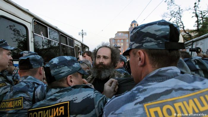 Russian policemen detain a participant of an Occupy protest in Moscow, Russia