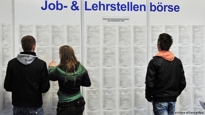 Young people stand in front of a job board