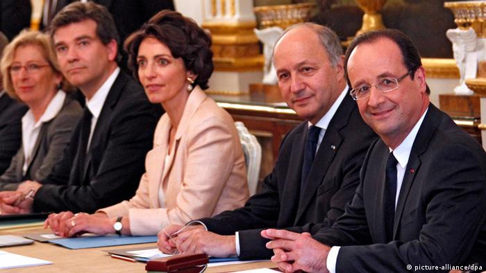 France's President Francois Hollande (R) flanked by key ministers in the cabinet