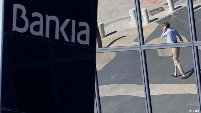 A man is seen reflected in the glass building of the Bankia bank headquarters in Madrid Photo:Paul White/AP/dapd