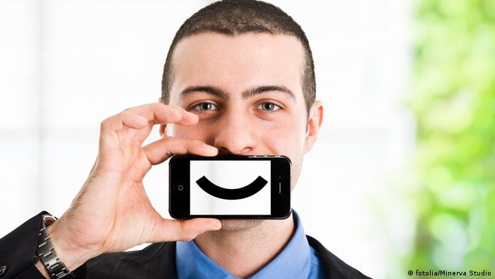 A man hold a mobile phone in front of his mouth with a smiley face painted on it