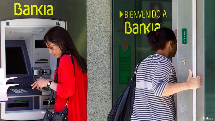A woman uses an ATM cash point machine at a branch of the Bankia bank in Madrid