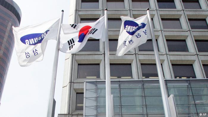 A pedestrian walks past under the Samsung flags at the headquarters of Samsung in Seoul, South Korea, Thursday, April 17, 2008. Special prosecutors probing alleged corruption at Samsung Group said Thursday they indicted Chairman Lee Kun-hee for tax evasion and breach of trust while clearing the conglomerate of bribery allegations. (ddp images/AP Photo/ Lee Jin-man).