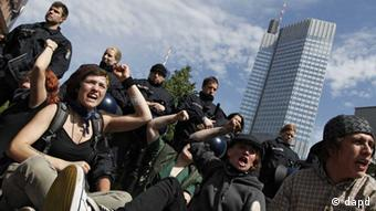 Protesters at sit-down event, with police officers and ECB tower in background