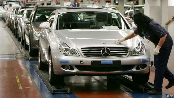 A DaimlerChrysler employee is polishing the hood of a new Mercedes Benz CLS car on the assembly line at the factory in Sindelfingen, southern Germany Photo/Thomas Kienzle