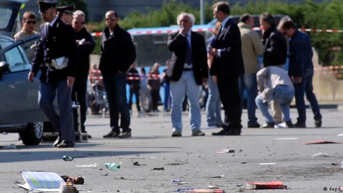 Italian policemen, background left, walk on the site where an explosive device went off outside Francesca Morvillo Falcone high school in Brindisi, Italy, Saturday, May 19, 2012. Several students were wounded. (Foto:Max Frigione/AP/dapd)