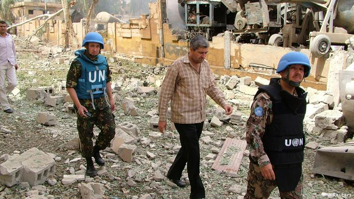 Members from the United Nations observers mission in Syria survey the damage after an explosion in Deir Ezzor
