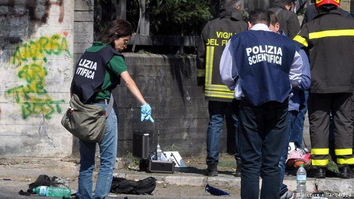 Firefighters and forensic officers investigate the scene in front of the school where a bomb exploded in Brindisi, southern Italy.
